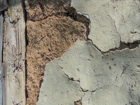 peeling white plaster from an old clay wooden wall