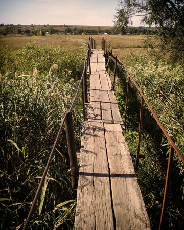 old wooden bridge with metal poles in a meadow with reeds Zdjęcie Seryjne