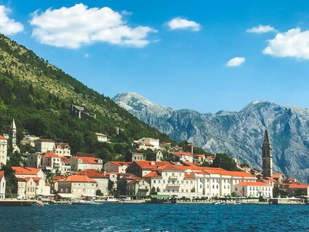 Panorama of the historic town of Perast in the Bay of Kotor on a beautiful sunny day with blue sky and clouds in summer. Montenegro Southern Europe. summer 2019