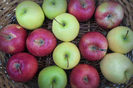red, green and yellow apples in a wicker basket top view