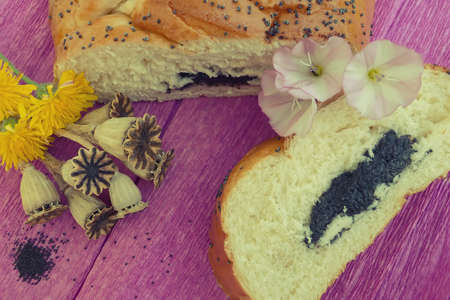 bun with poppy seeds and a piece of bun with yellow and pink flowers and dry poppy seed pods on a purple background. poppy festival Zdjęcie Seryjne