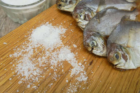 four dried piranhas lie on a board on which table salt is scattered