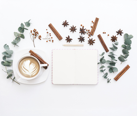 Flat lay composition with notebook, coffee and leaves. Morning concept.