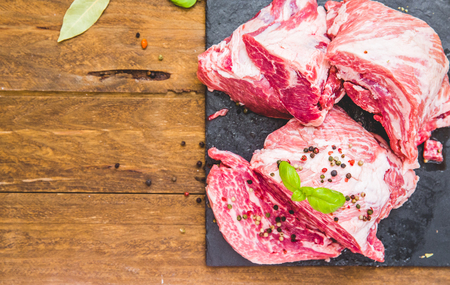 Fresh juicy meat with spices over wooden background