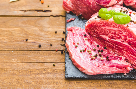 Fresh meat with spices over wooden background