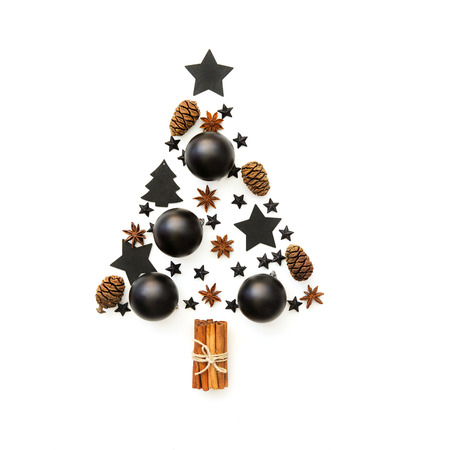 Christmas tree made from black decorations on white background. holiday and celebration creative concept. New Year and Christmas postcard or invitation. Flat lay  Stock Photo
