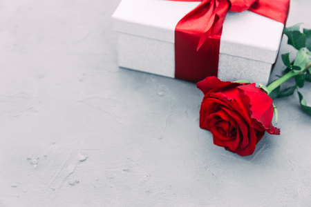Beautiful red rose and gift box on wooden background with copy space. valentines day present.