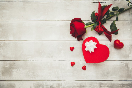 Gift box and red rose on wooden background. Valentines concept