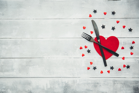 Top view valentines day.dinner set fork and knife, red ribbon and heart shape on wooden with copy space. Stock Photo