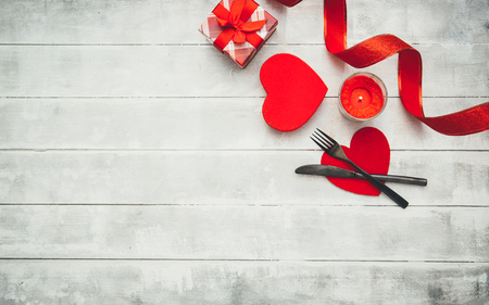 Valentines day table setting with  fork, knife, red hearts, ribbon and roses. Valentines day background or first date