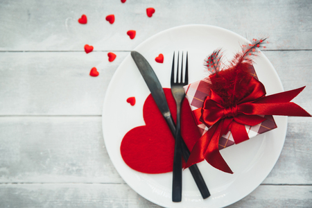 Valentines day table setting with plate, fork, knife, ribbon and rose. background