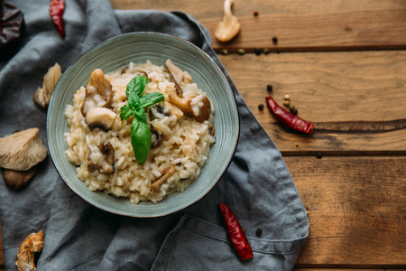 Risotto with mushrooms on an old wooden background. Rustic style. Stock Photo