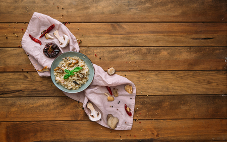 Risotto and mushroom dish in bowl over wooden table. Flat lay, top view, copy space