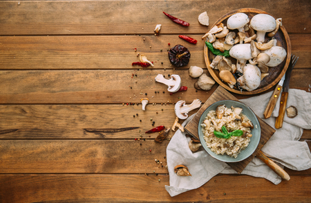 Risotto with mushrooms over wooden background. Top view with copy space