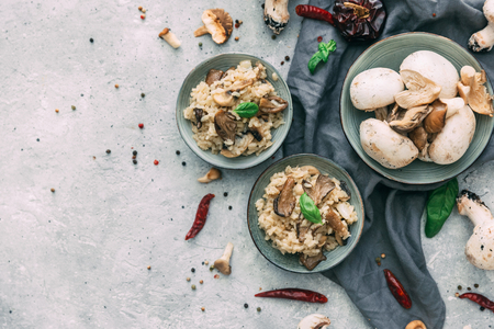 Risotto with porcini mushrooms on wooden background. Flat lay composition