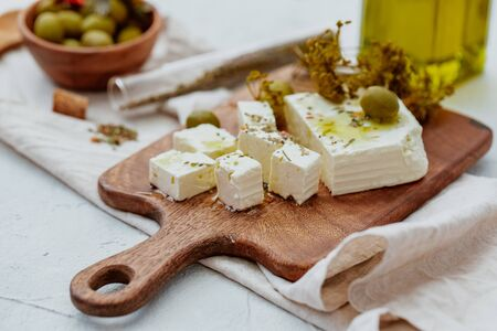 Fresh Greek Feta Cheese with olives. Healthy ingredient for cooking salad. Chopped Goat feta cheese on cutting board.