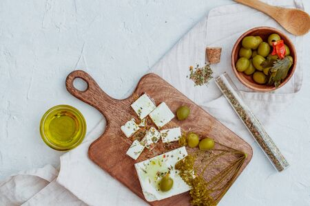Greek cheese feta with thyme and olives on wooden board.