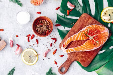 Fresh raw salmon steak with herbs and spices, top view