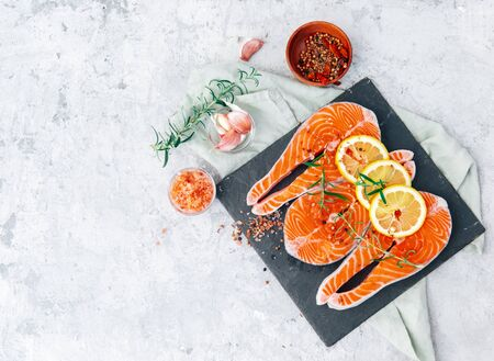 Fresh salmon fillet with aromatic herbs, spices and lemon. Balanced diet or cooking concept. Top view, flat lay