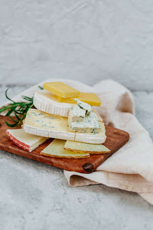 Different sorts of cheese, blue, brie, camembert and other with walnuts on wooden board background