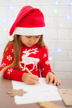 Adorable litle girl is writting a letter to Santa Klaus sitting on the table and wearing a hat of Santa with a white background