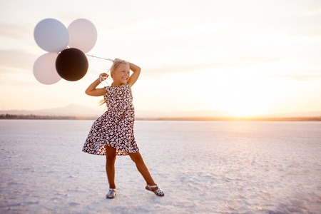 Little caucasian smiling girl with black and white baloons on salty lake in Larnaca on Cyprus, standing on the left side 版權商用圖片
