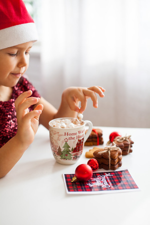 Little girl in Santa hat eating marshmallow from mug with cacao and cookies Christmas card and red balls on table near, Merry Cristmas Stock Photo