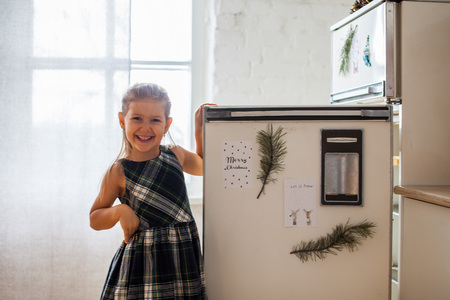 Merry Christmas, little happt smiling girl with opened refrigerator with Christmas cards on it, opposite the light