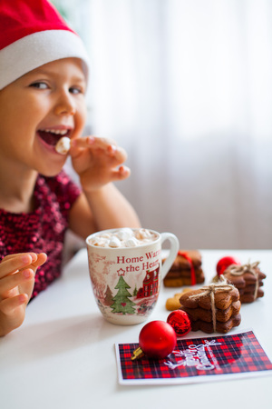 Little girl in Santa hat eating marshmallow from mug with cacao and cookies Christmas card and red balls near, Merry Cristmas