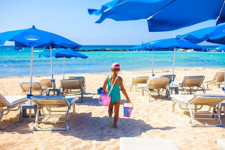 Little girl walking to the beach with beach bag and toys, sunbeds and umbrellas on background