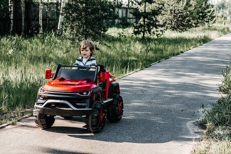 curly-haired boy in a striped T-shirt rides a red big toy car driving on an asphalt path. day off, outdoor recreation 免版税图像