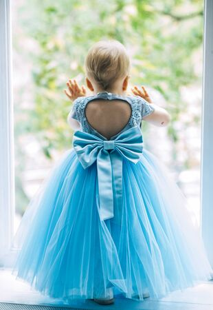 little girl in a blue magnificent princess dress. Birthday is one year. the child learns to walk. studio photo session
