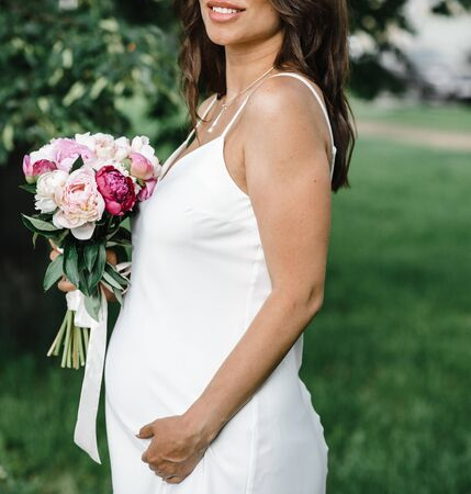 pregnant bride in a white thin dress on thin straps with bare shoulders with a bouquet of peonies. motherhood
