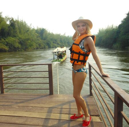 young blonde woman in a life jacket and swimsuit. water holidays vacations on the river pond river safety