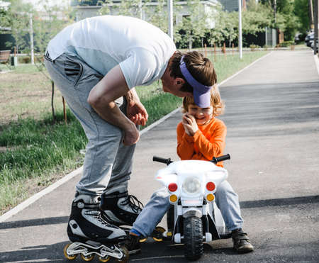 father and son for a walk. boy on a toy children motorcycle dad roller skate. family holiday. father day
