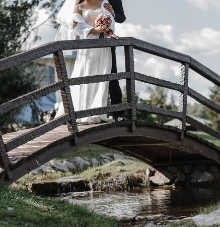 young couple of newlyweds stands embracing on a wooden bridge. bride in a white dress with a wedding bouquet Zdjęcie Seryjne