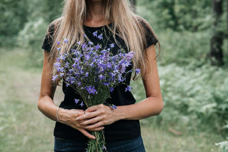 young woman with long hair holds in her hands a bouquet of wildflowers of blue color. rural meadows, farm Stok Fotoğraf