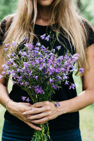 young woman with long hair holds in her hands a bouquet of wildflowers of blue color. rural meadows, farm Standard-Bild