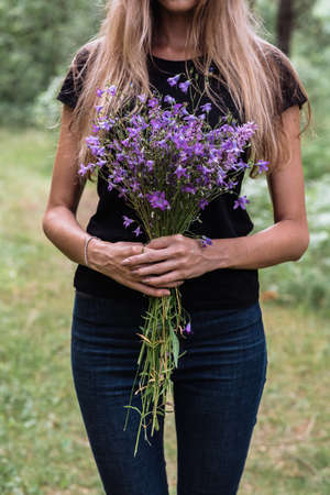 young woman with long hair holds in her hands a bouquet of wildflowers of blue color. rural meadows, farm 版權商用圖片