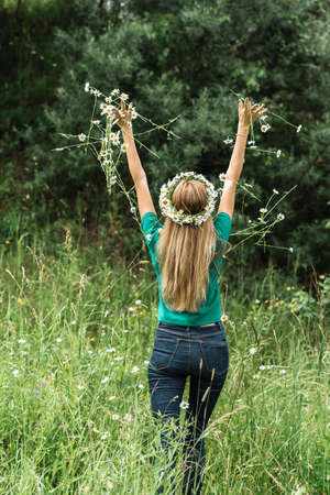 a young woman in a wreath on her head with long hair stands with her back and throws up a bouquet of wildflowers