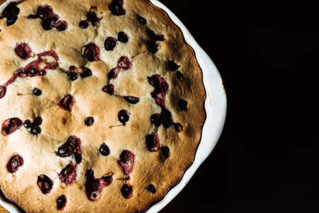 cooked homemade pie with berries in a white baking dish on a black background. Homemade sweets, homemade pie, cake Banco de Imagens
