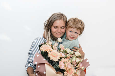son and young mother hug and kiss. the child congratulated his mother on her birthday and presented bouquet Stock fotó