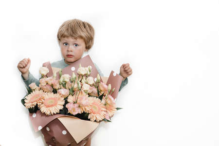 boy child with flowers on a white background congratulated mom on her birthday Stock fotó