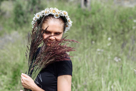 young woman with a wreath of daisies on her head in the sun on a field of grass Stockfoto
