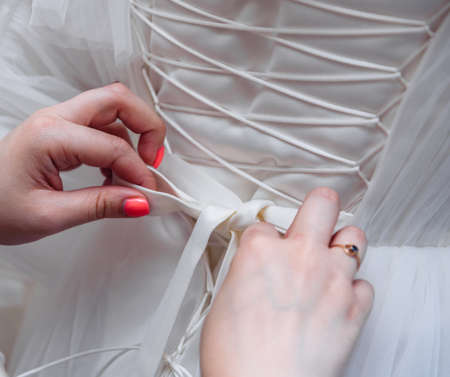 gathering the bride wedding preparation bridesmaid helps to put on a dress with a corset and lacing