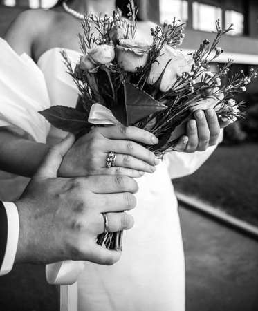 brides hand with an elegant wedding ring with white gold diamonds on a bouquet