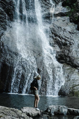 young woman on the background of a mountain waterfall with a ponytail