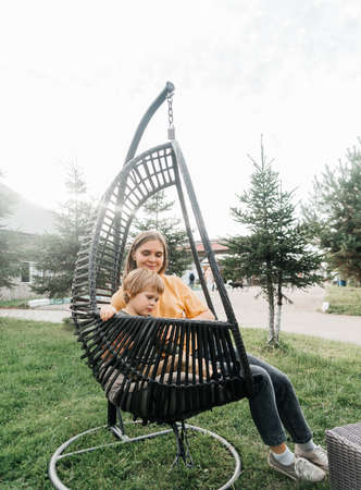 mother and child ride on a wicker rattan cocoon swing. son shakes a woman, shakes a summer vacation in nature