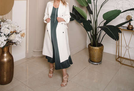 Beautiful blonde woman natural make up wear fashion clothes casual dress code office style white long cloak for romantic date business meeting interior boho stairs flowerpot.