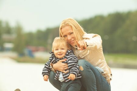 A mother with long hair gently holds her little son in her arms. Photo in the park with natural light